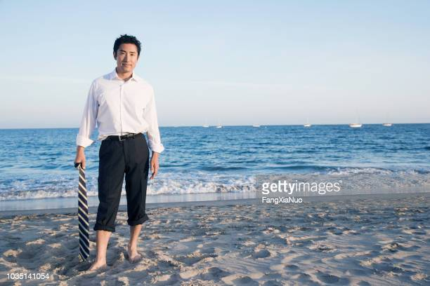 asian businessman standing on beach - wading stock pictures, royalty-free photos & images
