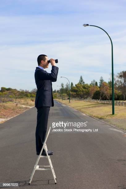 Asian businessman standing on ladder with binoculars