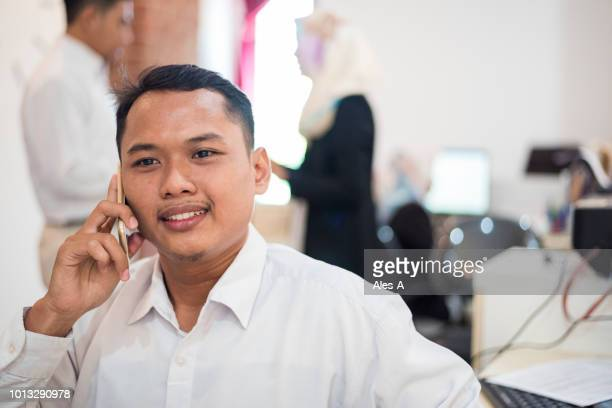 asian businessman talking on his cell phone - indonesia stock pictures, royalty-free photos & images