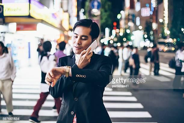 Asian businessman talking on smart phone on street bu night