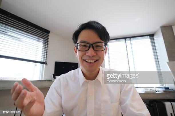 自宅からビデオ会議で話すアジアのビジネスマン - 遠隔会議 ストックフォトと画像