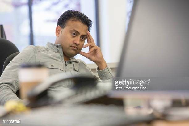 asian businessman thinking at desk in office - irritation stock pictures, royalty-free photos & images