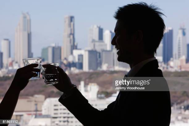 Asian businessman toasting next to window