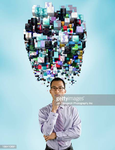 Asian businessman underneath cloud of technology images