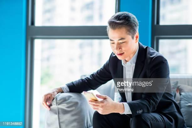 asiatischer geschäftsmann nutzt smartphone - koreanischer abstammung stock-fotos und bilder