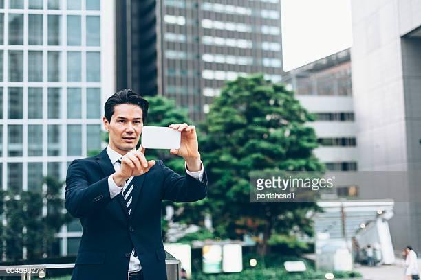 Asian businessman using smart phone on the street