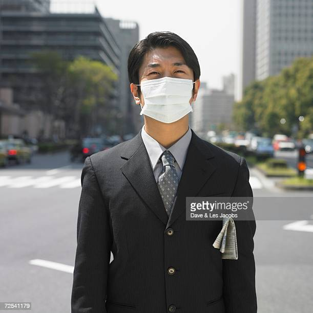 Asian businessman wearing surgical mask in urban area