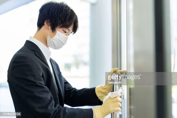 手袋拭くドアを持つアジアのビジネスマン - 殺菌 ストックフォトと画像