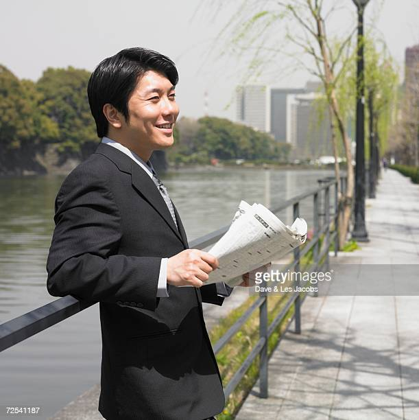Asian businessman with newspaper in urban park
