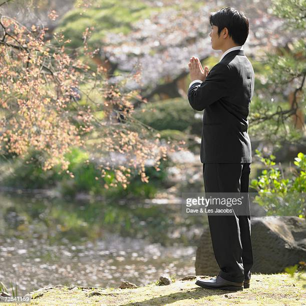 Asian businessman with palm together in front of heart in park