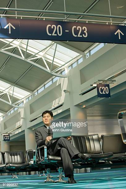 Asian businessman works on computer at airport.