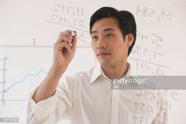 Asian businessman writing on white board
