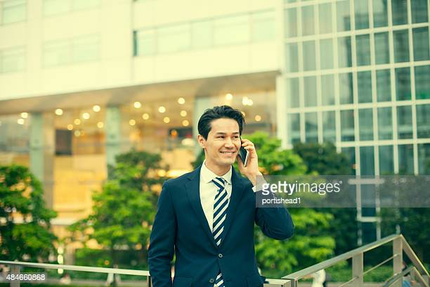 asian businessmen answering on his mobile phone - one mid adult man only stock pictures, royalty-free photos & images