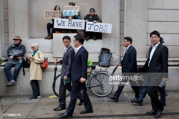 Asian businessmen look at environmental activists protesting about Climate Change during the blockade outside the Bank of England in the heart of the...