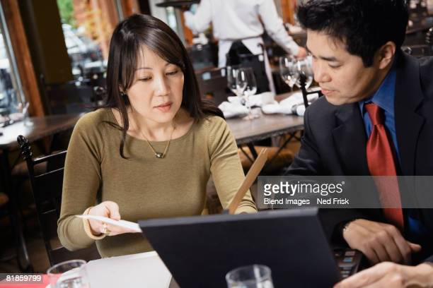 Asian businesspeople looking at paperwork