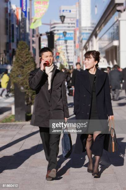 asian businesspeople walking on sidewalk - 歩行者 ストックフォトと画像