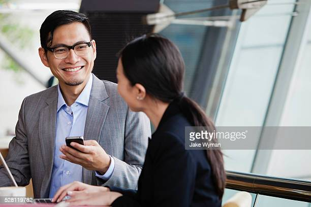 Asian businesswoman & businessman in a cafe in Hong Kong.