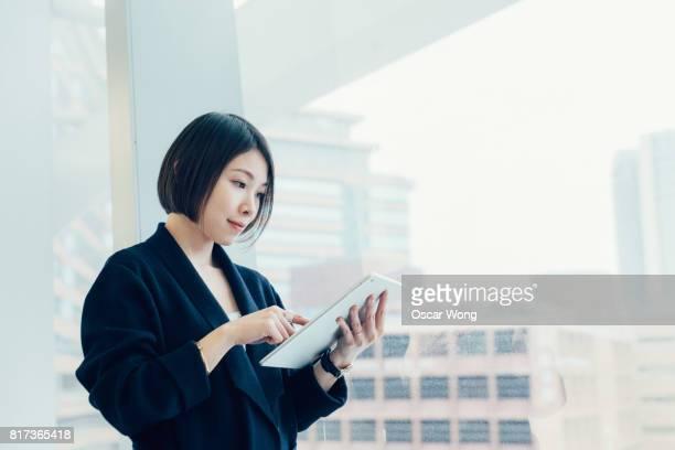 Asian businesswoman checking stock market on digital tablet