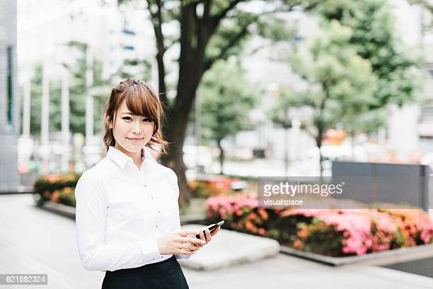 Asian Businesswoman Holding a Phone with a Smile