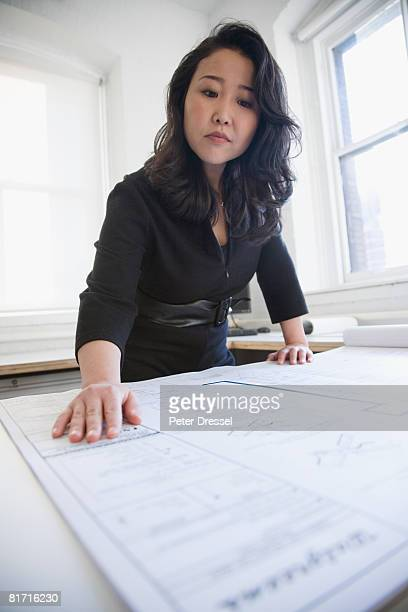 Asian businesswoman looking at blueprints