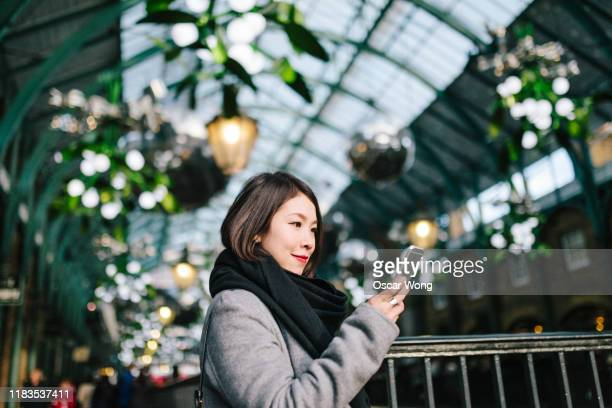 asian businesswoman looking her phone in christmas market - shopping centre stock pictures, royalty-free photos & images