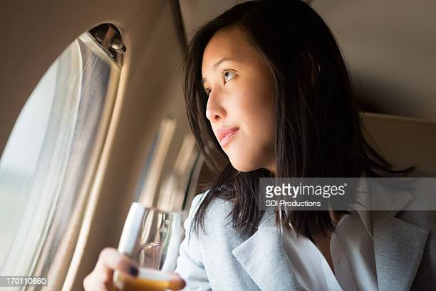 Asian businesswoman looking through window of private jet, sipping champagne