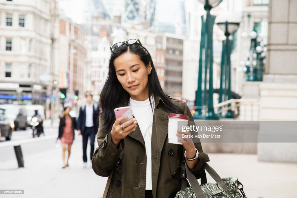 Asian businesswoman looks at smart phone while walking in city. : Stock Photo