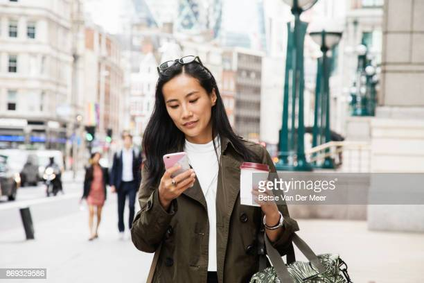 asian businesswoman looks at smart phone while walking in city. - asian drink stock photos and pictures