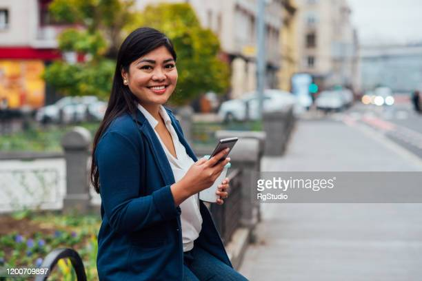 asian businesswoman on a coffee break using smartphone - international womens day stock pictures, royalty-free photos & images