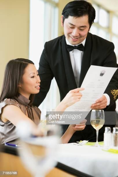 Asian businesswoman ordering meal in restaurant
