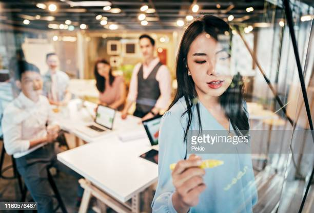 asian businesswoman presenting her ideas for company development - asian stock pictures, royalty-free photos & images