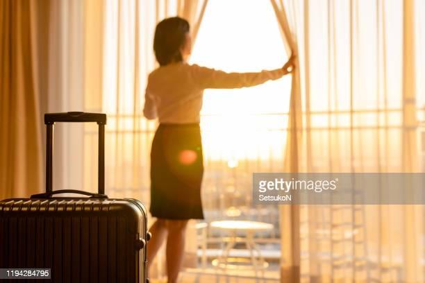 mulher de negócios asiática que puxa as cortinas para ver a vista - hóspede - fotografias e filmes do acervo