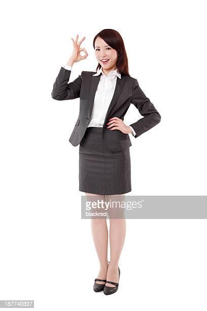 アジア Ok の標識を示すビジネスウーマンに白背景