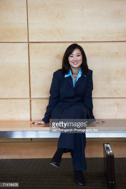 Asian businesswoman sitting on bench indoors