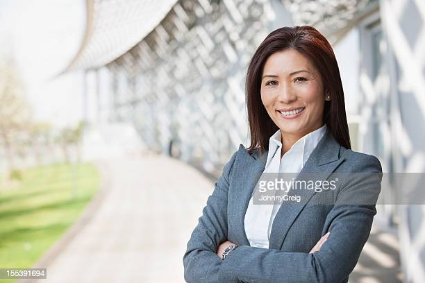 Asian Businesswoman Smiling With Arms Crossed