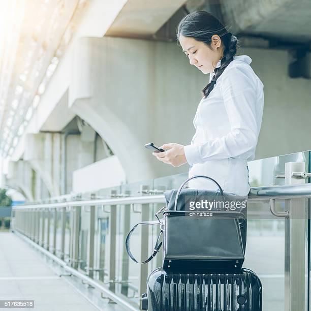 asian businesswoman typing on the cellphone - transportation building type of building stock photos and pictures