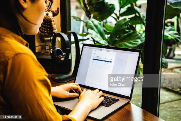 asian businesswoman using a laptop to write a report - obscured face stock pictures, royalty-free photos & images