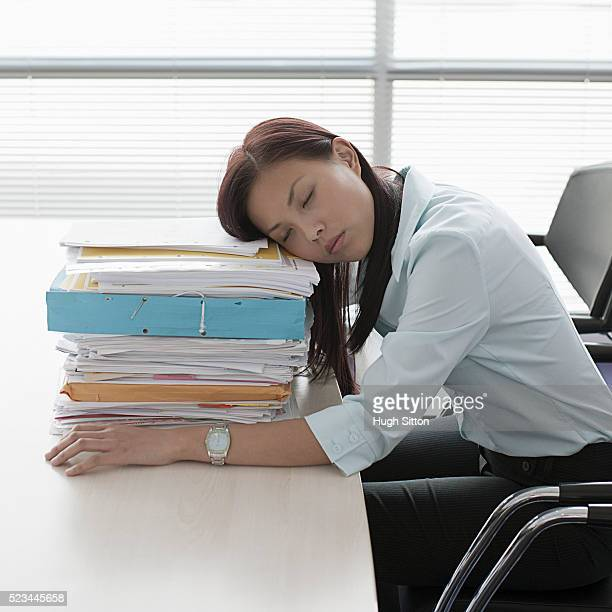 asian businesswoman with a lot of paperwork asleep at her desk - hugh sitton stock pictures, royalty-free photos & images