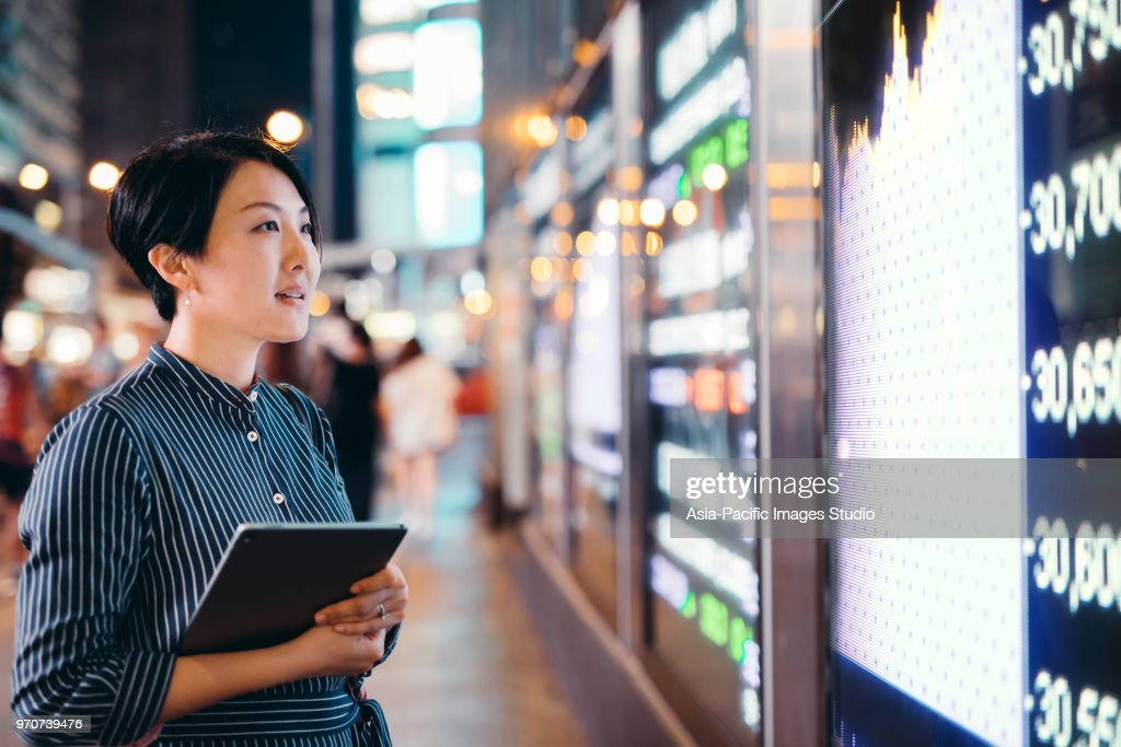 Asian businesswomen checking stock market data on tablet before Hong Kong financial display board : Stock Photo