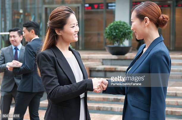 Asian Businesswomen Shaking Hands in Financial District