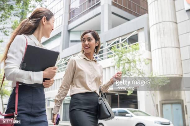 Asiatiska affärskvinnor promenader i modern stad gatan
