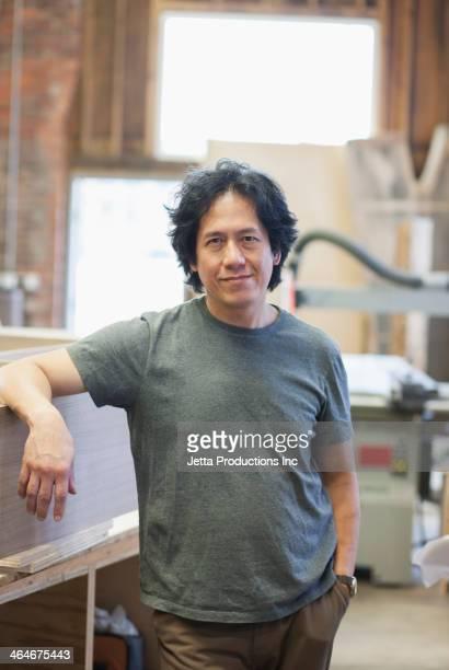 Asian carpenter smiling in workshop