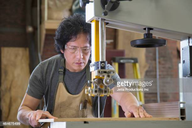 Asian carpenter using cutting machine in workshop