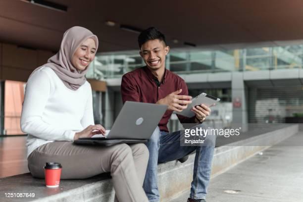 aziatische toevallige zaken op de gaan gebruikend laptop buiten bureau - zuidoost aziatische etniciteit stockfoto's en -beelden
