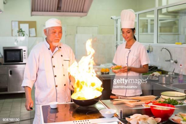 アジアのシェフと助手調理し、火災