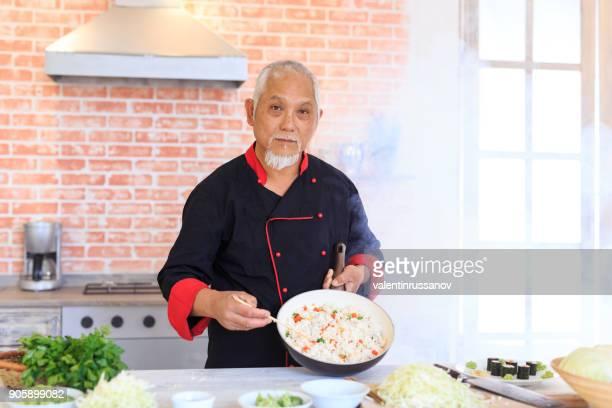 Chef asiatique préparation du riz aux légumes