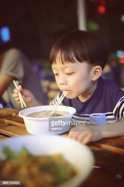 Asian child eating delicious noodle with chopstick