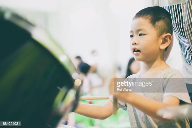 Asian child learning drum kit