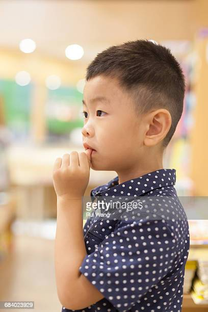 Asian child looking with finger biting