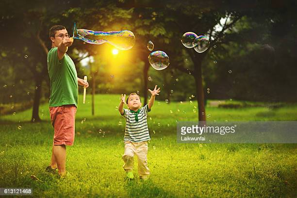 Asian child playing bubble wand with father
